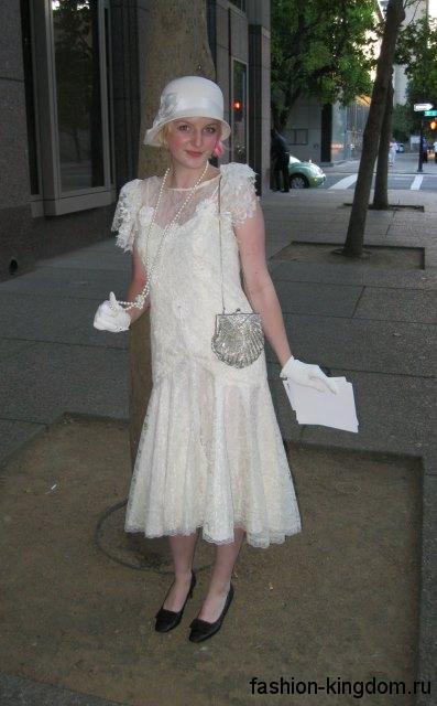 Белое платье-миди в стиле 1920, прямого кроя, украшенное ажурными вставками, в тандеме с ниткой жемчуга и шляпой клош.