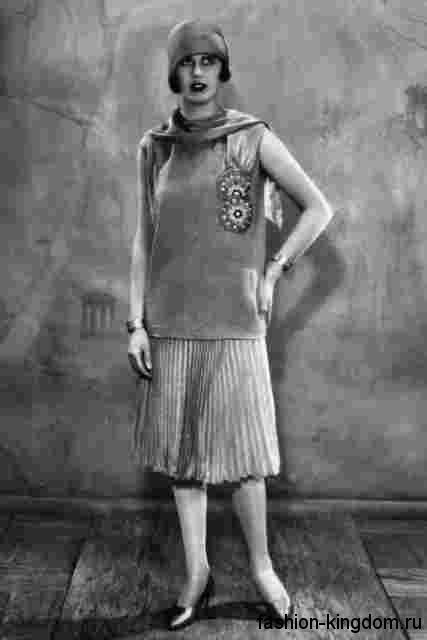 Юбка-плиссе 1920 годов длиной чуть ниже колен в тандеме с прямой блузой без рукавов, шляпой клош и туфлями на низком каблуке.