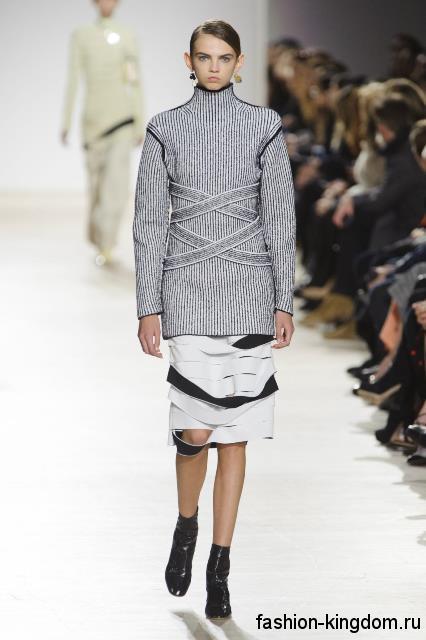 Удлиненный свитер серого цвета сочетается с юбкой-миди черно-белого тона и лаковыми сапогами из коллекции осень 2016 от Proenza Schouler.