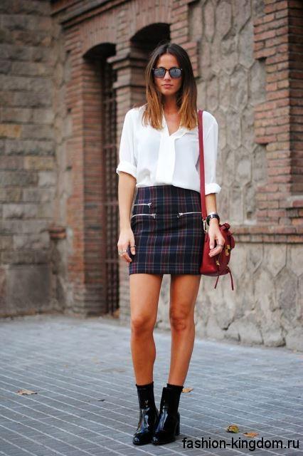 Короткая юбка черно-красного тона в клетку, облегающего фасона сочетается с шифоновой белой блузкой.