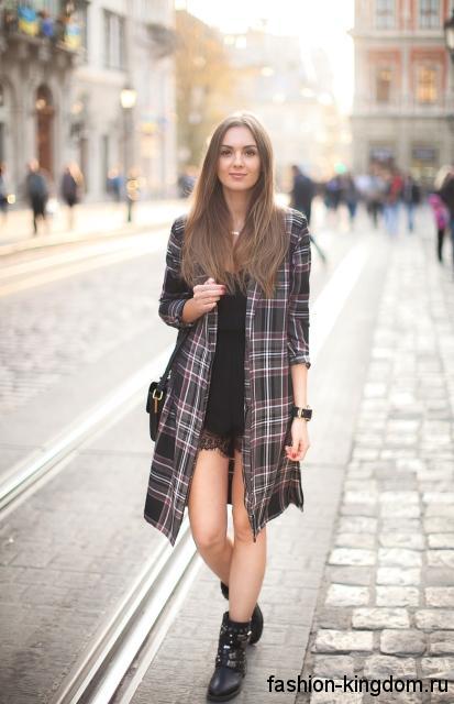Легкое осеннее пальто черного цвета в клетку, прямого фасона, длиной до колен сочетается с кожаными ботинками.