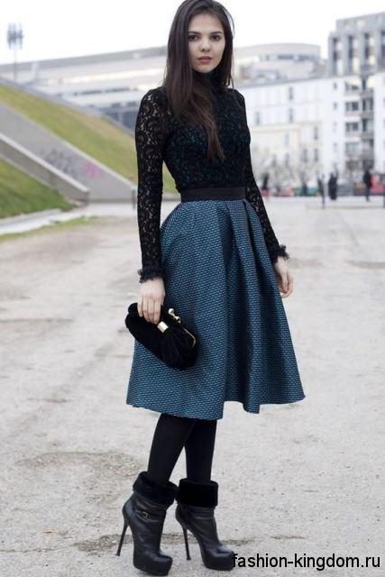 Вечерняя юбка темно-синего цвета, расширенного фасона, длиной до колен в сочетании с ажурной черной блузкой.