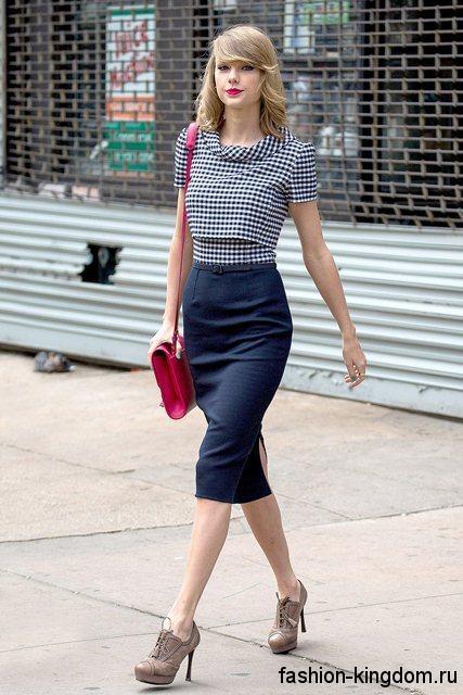 Офисная юбка-карандаш иссиня-черного цвета, длиной до колен в сочетании с черно-белой блузкой в клетку.