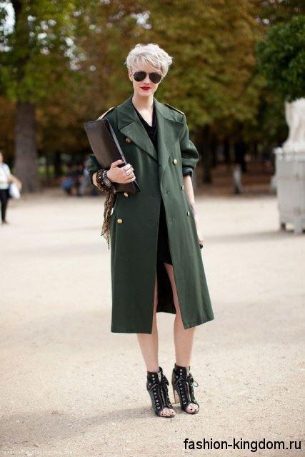 Осеннее пальто в стиле милитари зеленого цвета, прямого фасона, длиной ниже колен в сочетании с коротким платьем.
