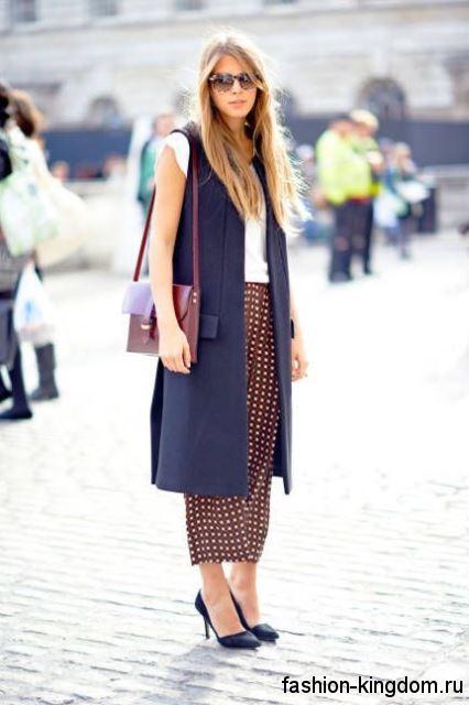 Осеннее пальто длиной миди без рукавов, темно-синего цвета, прямого фасона в тандеме с черными туфлями на каблуке.