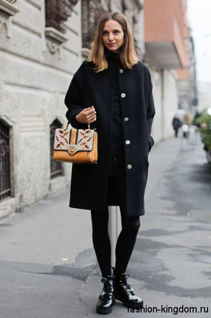 Черное осеннее пальто на каждый день, прямого фасона, длиной чуть выше колен сочетается с лакированными ботинками.