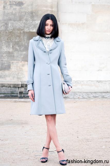 Осеннее пальто голубого цвета, приталенного фасона, длиной до колен сочетается с синими босоножками.