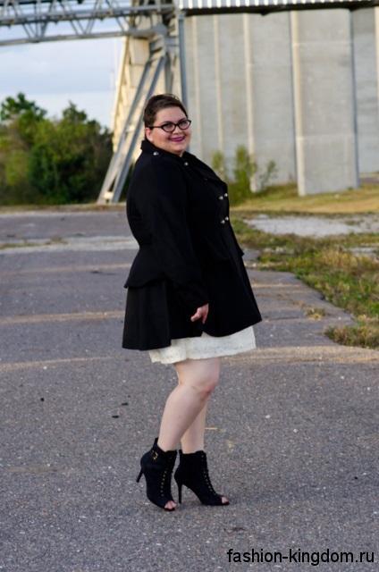 Осеннее черное пальто для полных девушек, приталенного кроя в сочетании с открытыми черными ботильонами.