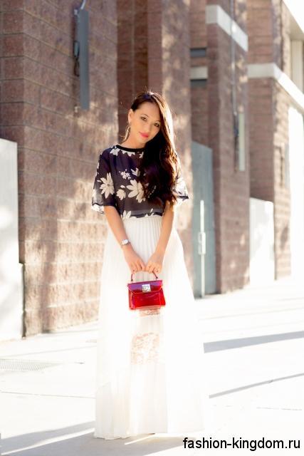 Длинная вечерняя юбка белого цвета, свободного силуэта сочетается с шифоновой черной блузкой с принтом.