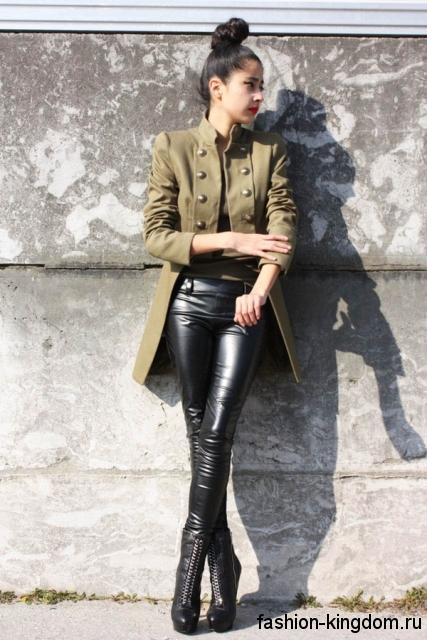 Асимметричное осеннее пальто в стиле милитари, болотного цвета, с пуговицами сочетается с кожаными брюками.