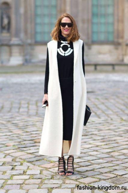 Длинное осеннее пальто без рукавов, белого цвета, свободного кроя сочетается с длинным черным платьем.