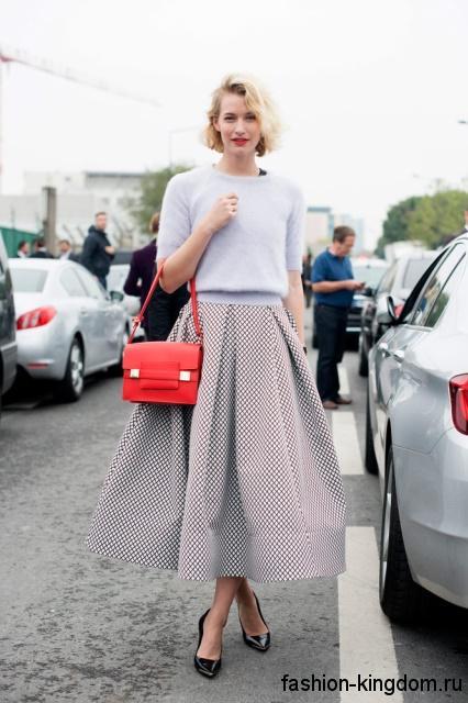 Длинная юбка черно-белого цвета в мелкую клетку, расклешенного фасона в тандеме со светло-голубой кофточкой.