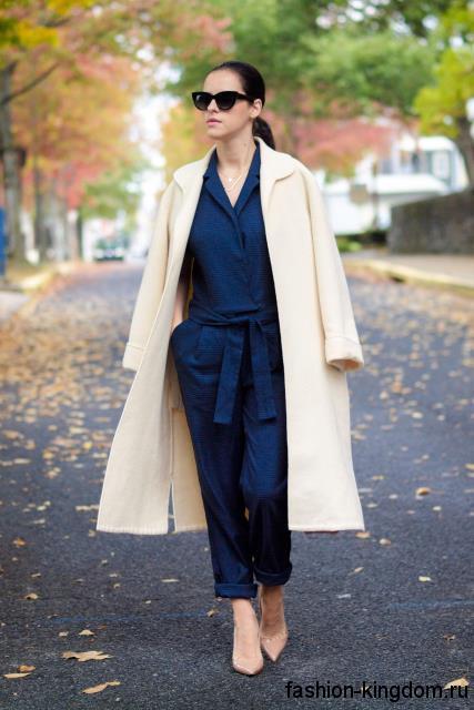 Осеннее пальто бежевого цвета в офис, классического фасона, длиной миди сочетается с темно-синим комбинезоном.