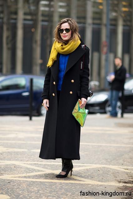 Длинное осеннее пальто в стиле милитари, черного цвета, свободного кроя в сочетании с широким желтым шарфом.