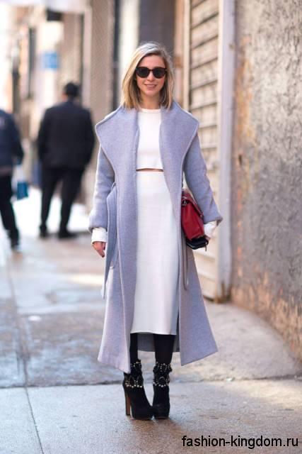 Длинное осеннее пальто светло-серого цвета, приталенного кроя в сочетании с сапогами черного тона на каблуке.