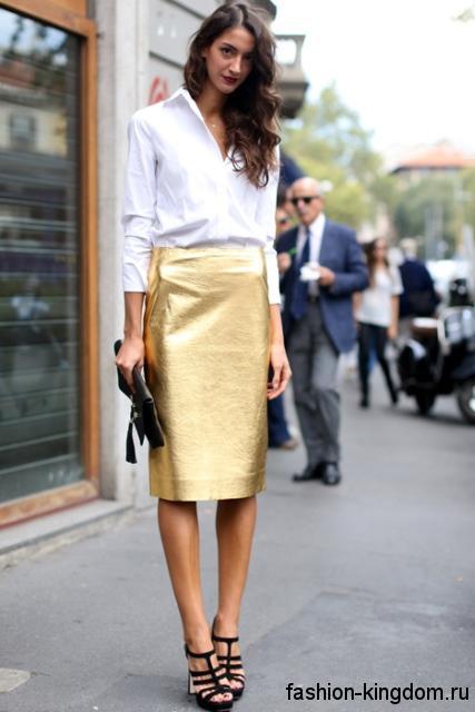 Вечерняя юбка-миди прямого кроя, золотистого цвета в сочетании с белой рубашкой с длинными рукавами.