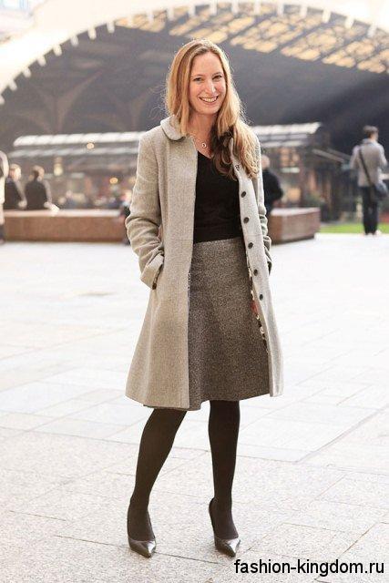 Серая офисная юбка-миди трапециевидного фасона сочетается с черной блузкой и пальто светло-серого оттенка.