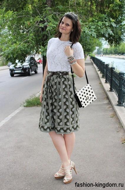 Юбка до колен темно-зеленого цвета с белым принтом сочетается с ажурной белой блузой с короткими рукавами.