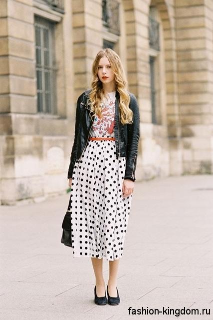Повседневная юбка-миди белого цвета в черный горошек, прямого кроя сочетается с кожаной курткой.