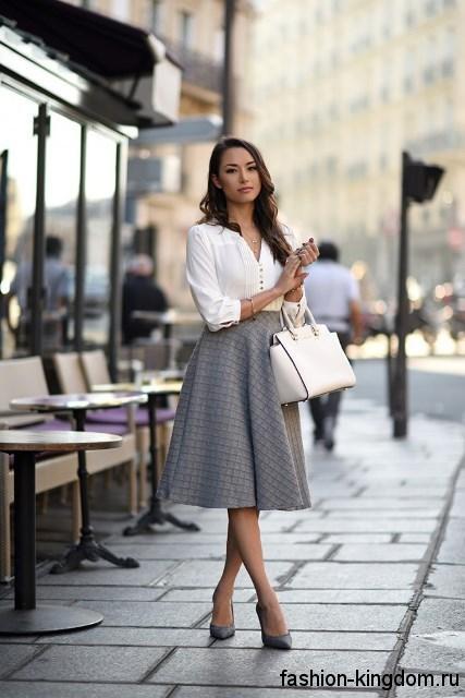 Офисная юбка-миди серого цвета, расширенного силуэта сочетается с белой блузкой с рукавами три четверти.