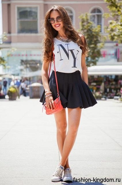 Юбка-мини черного цвета в складку в сочетании с белой футболкой и кедами белого тона.