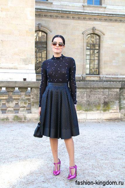 Вечерняя черная юбка в складку, длиной до колен сочетается с полупрозрачной черно блузкой с длинными рукавами.