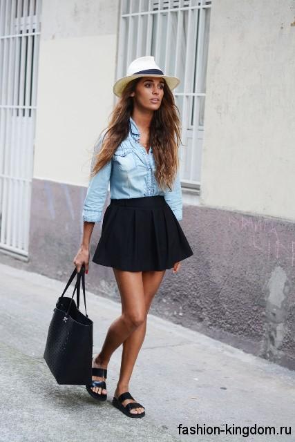 Короткая повседневная юбка черного цвета в складку в сочетании с джинсовой рубашкой голубого тона.