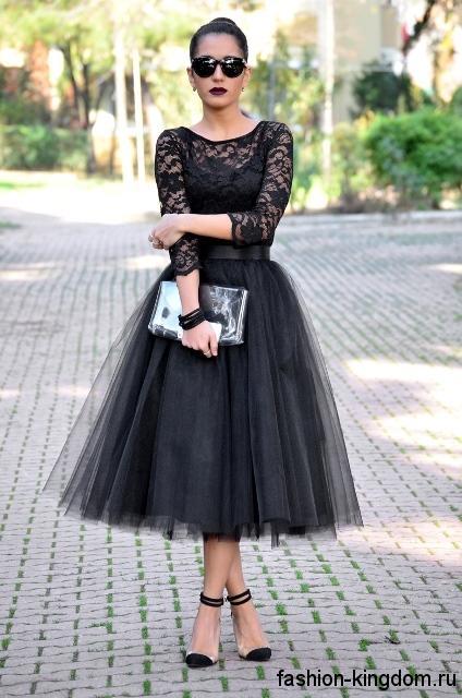 Пышная длинная юбка черного цвета в сочетании с кружевной блузкой черного тона с рукавами три четверти.