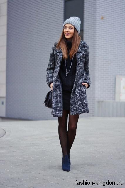 Осеннее пальто темно-серого цвета в клетку, приталенного фасона, длиной выше колен сочетается с ботильонами на каблуке.