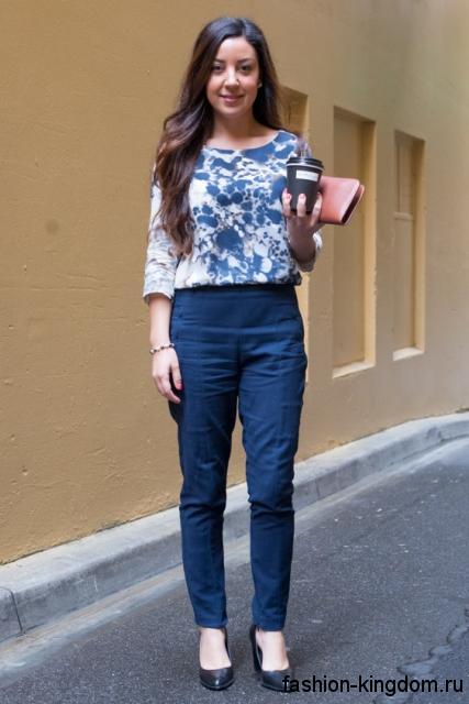 Офисные брюки темно-синего цвета, прямого кроя для невысоких женщин сочетаются с блузой бело-синей расцветки.