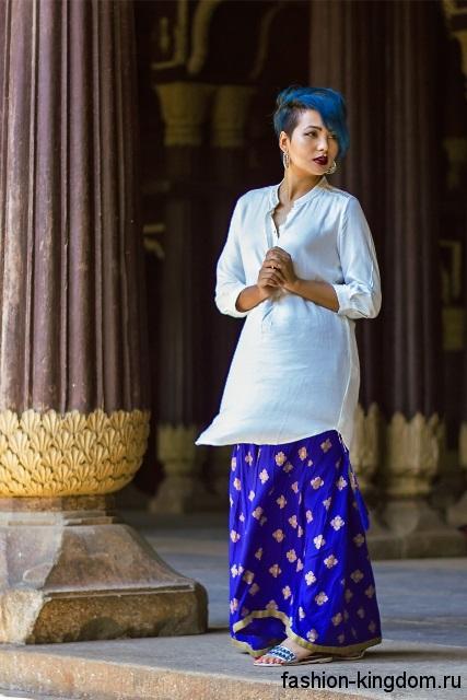 Юбка макси синего цвета с золотистым принтом в этническом стиле сочетается с длинной белой блузкой широкого фасона.