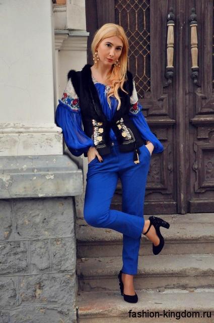 Шифоновая блузка синего цвета в стиле этно в сочетании с меховой жилеткой и синими узкими брюками.