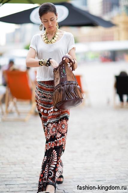 Длинная юбка черно-коричневого тона с принтом в стиле этно сочетается с топом белого цвета.
