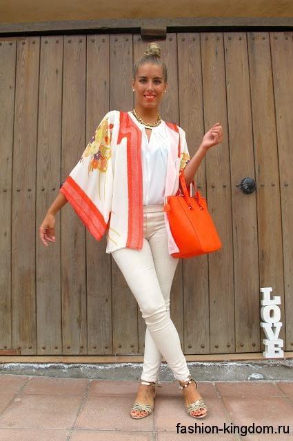 Тонкий кардиган бело-оранжевого цвета, широкого фасона в этническом стиле в тандеме с узкими белыми брюками.