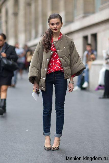 Узкие синие джинсы для невысоких женщин в сочетании с объемной курткой цвета хаки и туфлями на каблуке.