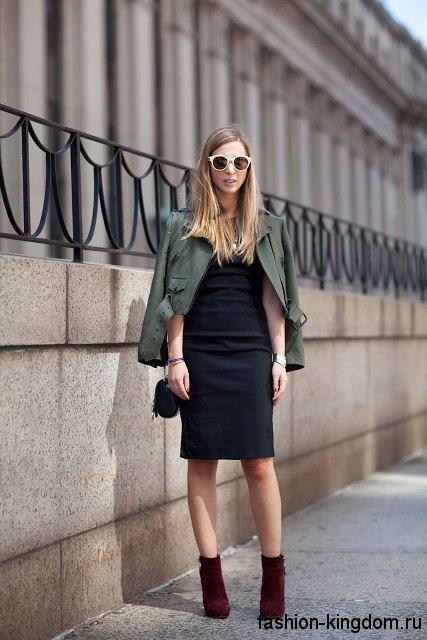 Черное платье-футляр длиной до колен для невысоких женщин в сочетании с короткой курткой цвета хаки.