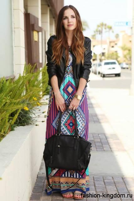 Длинное платье с геометрическим принтом, прямого кроя в этническом стиле сочетается с кожаной черной курткой.
