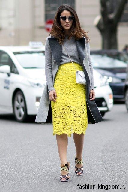 Ажурная желтая юбка прямого кроя, длиной ниже колен для невысоких женщин в сочетании с длинным кардиганом серого цвета.