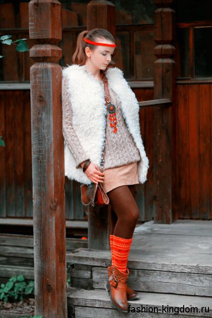 Меховая белая жилетка свободного фасона в стиле этно сочетается с вязаным свитером бежевого тона и короткой юбкой.