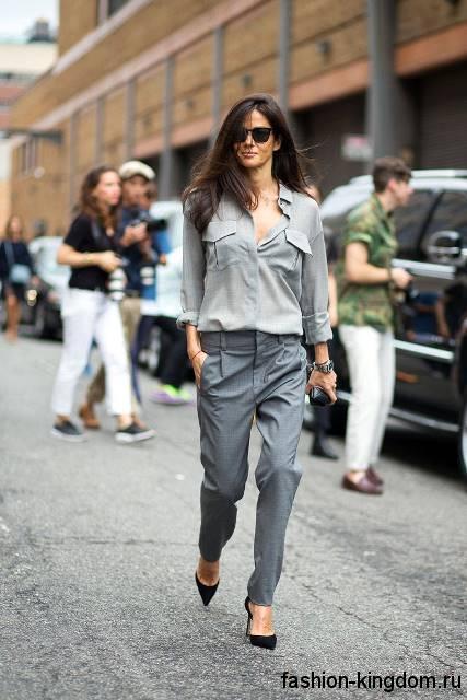 Офисные брюки серого цвета, прямого кроя для невысоких женщин в сочетании с блузкой светло-серого тона с длинными рукавами.