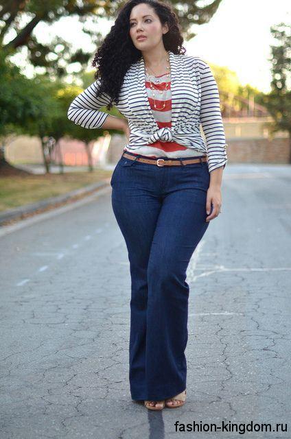 Джинсы-клеш синего цвета в сочетании с тонкой кофточкой черно-белого тона в полоску для невысоких женщин.