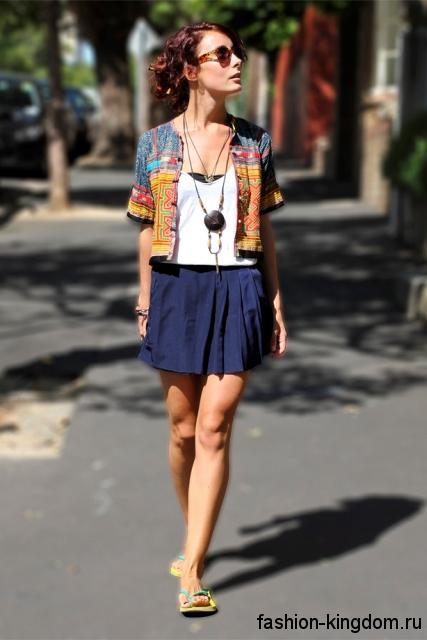 Короткий разноцветный жакет прямого кроя, с короткими рукавами, в этническом стиле в тандеме с синей юбкой-мини.