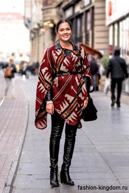 Осеннее пончо красного тона с принтом в этническом стиле дополняется высокими кожаными сапогами.
