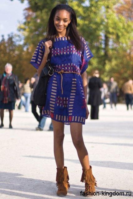 Короткие сапоги коричневого цвета с бахромой в этническом стиле сочетаются с коротким платьем синего тона.
