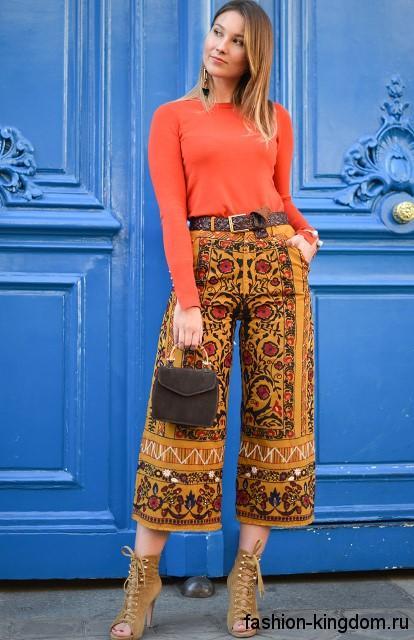 Короткие брюки горчичного цвета с растительным узором, широкого кроя в этническом стиле в сочетании с оранжевой блузой.
