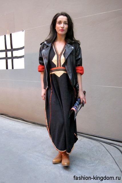 Длинное осеннее платье черного тона, свободного кроя в стиле этно сочетается с кожаной курткой черного цвета.
