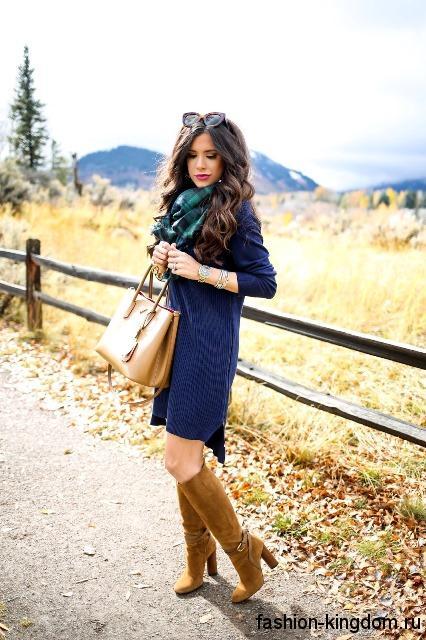 Теплое платье синего цвета, свободного кроя, длиной вше колен в сочетании с высокими сапогами.