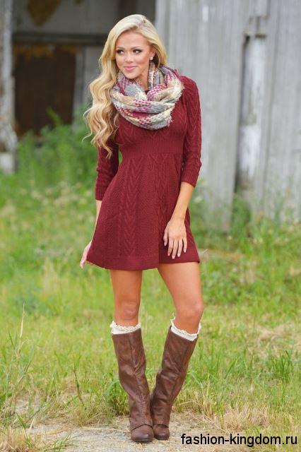Короткое теплое платье красного цвета, выше колен, с длинными рукавами в сочетании с высокими сапогами.