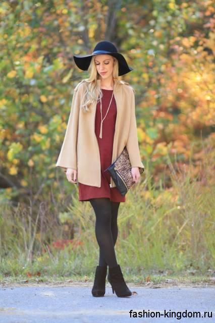Осеннее теплое платье бордового цвета, прямого силуэта, длиной выше колен в сочетании с черными ботильонами на каблуке.