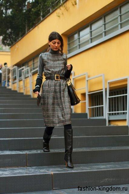 Клетчатое теплое платье серого цвета, полуприталенного кроя, длиной до колен сочетается с высокими сапогами.